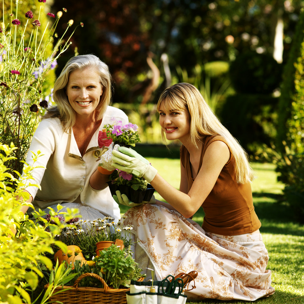 Elderly Woman And Young Woman Tending To Flowers In A